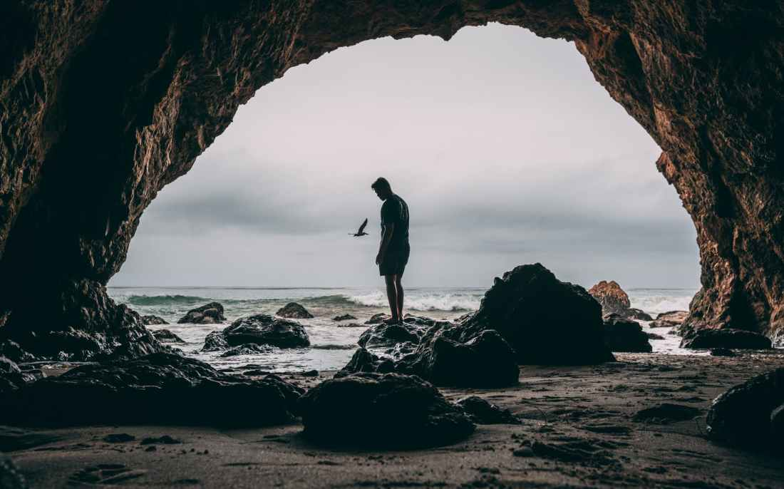 photo of man standing on rock near seashore